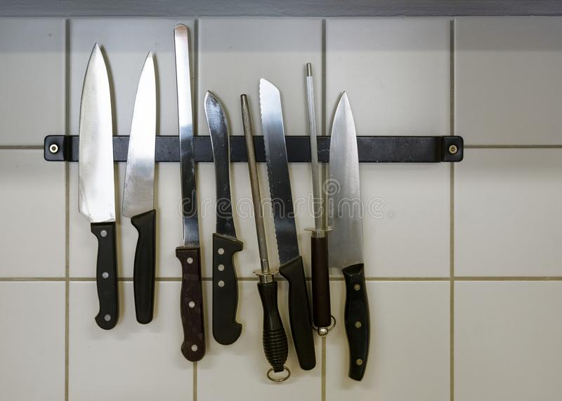 Large kitchen knives and honing steels hanging on a magnetic holder on the tiled wall, copy space royalty free stock image