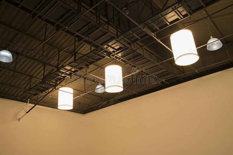 Large lamp hanging on ceiling in studio. Black steel roof frame. Sturdy stock photography