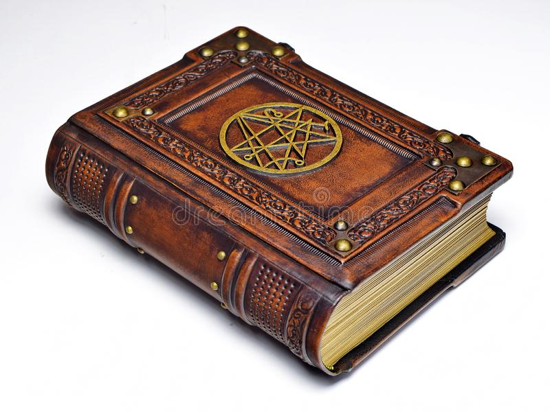 Large leather book, rich decorated with the gilded symbol the Sigil of the Gateway on the front cover. Captured from the left side while lay down to the table royalty free stock photography