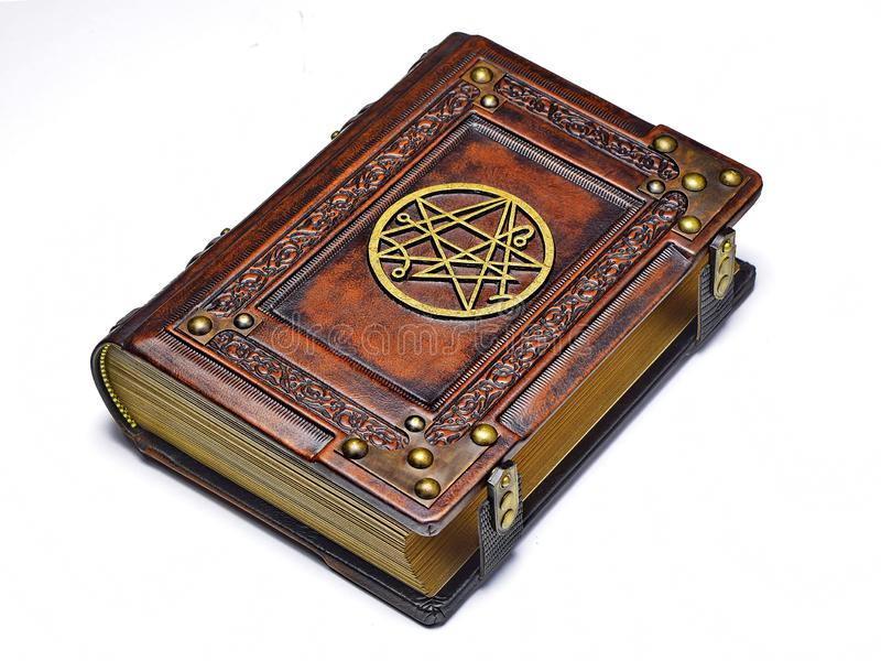 Large leather book, rich decorated with the gilded symbol the Sigil of the Gateway on the front cover. Captured from the right side whilelay down to the table royalty free stock photos