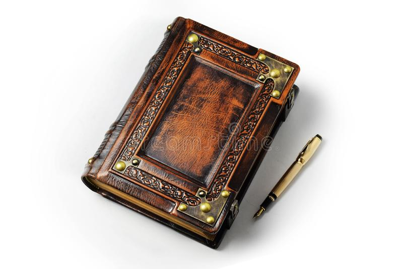 Large leather journal with the gold fountain pen in the book shadow stock images