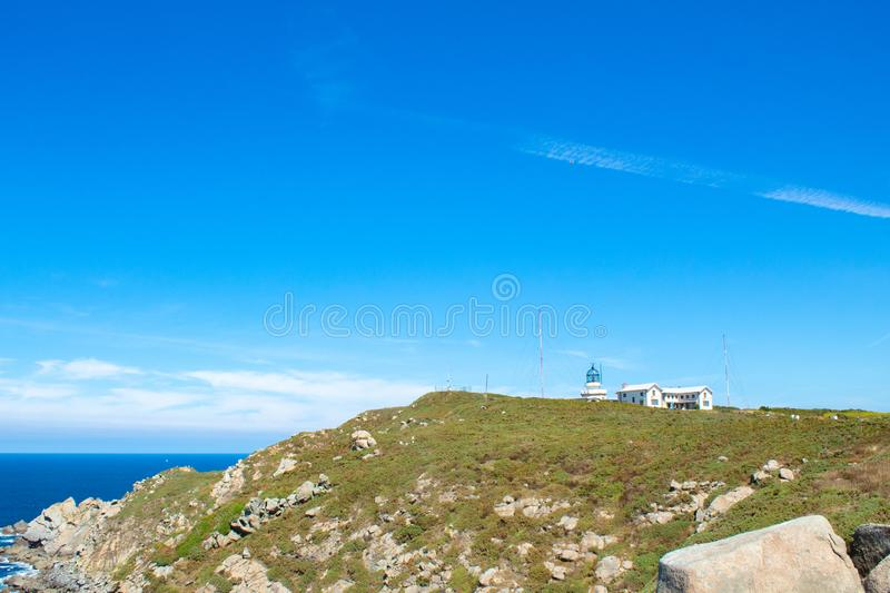 Lighthouse in the horizon. A large lighthouse with a glass dome on a sunny summer day royalty free stock photography