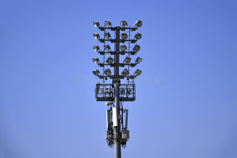 Large lighting tower with spotlights and loudspeakers installed against bright blue cloudless sky. stock photo
