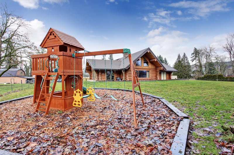 Large log cabin house exterior with kids playground. stock photos