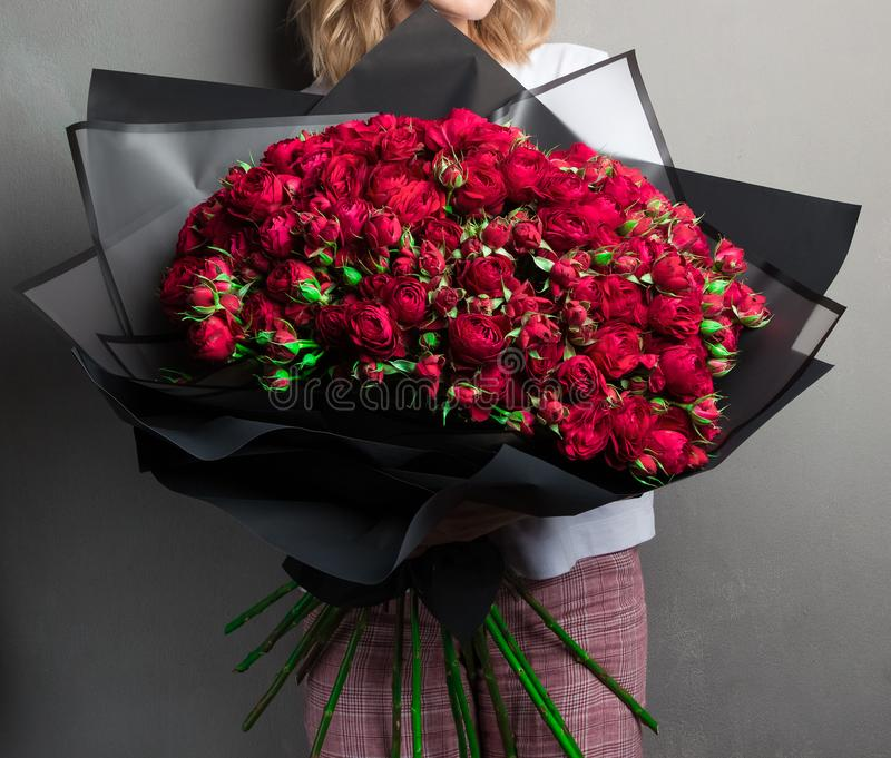 A large lush bouquet of red garden roses and buds in black wrapping paper, a stylish stock image