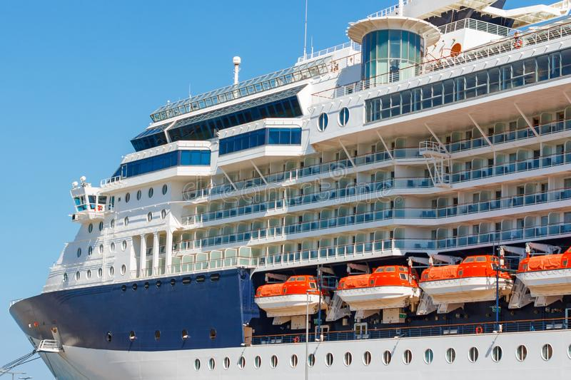 A large luxury cruise liner moored in the port of the Adriatic Sea, is waiting for passengers. There are four orange lifeboats. A large cruise liner moored in stock image