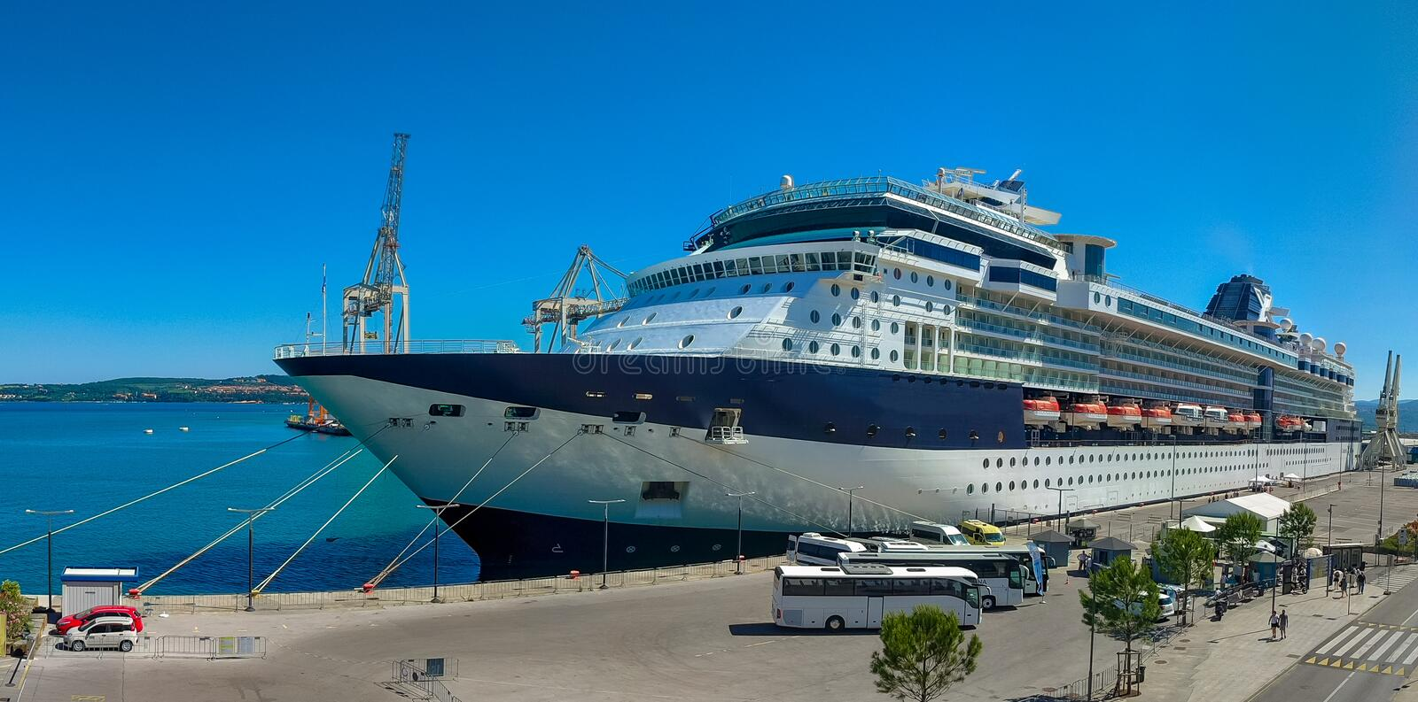 A large luxury cruise liner moored in the port of the Adriatic Sea, is waiting for passengers. There are four orange lifeboats. A large cruise liner moored in stock photography