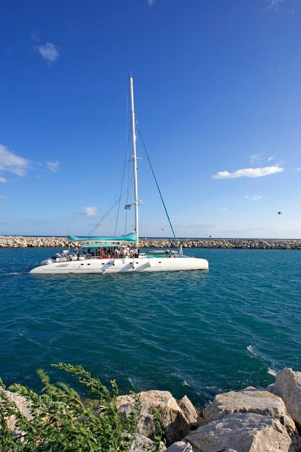 Large, luxury white catamaran leaving Puerto Banus harbour