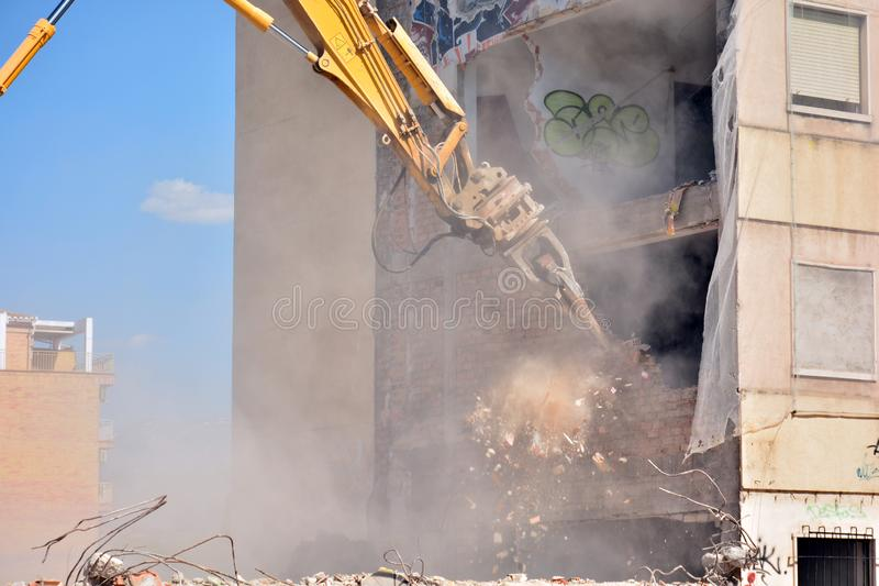 Arm of machine demolishing an apartment building. Large machine demolishing walls and pillars of an old residential building royalty free stock photos