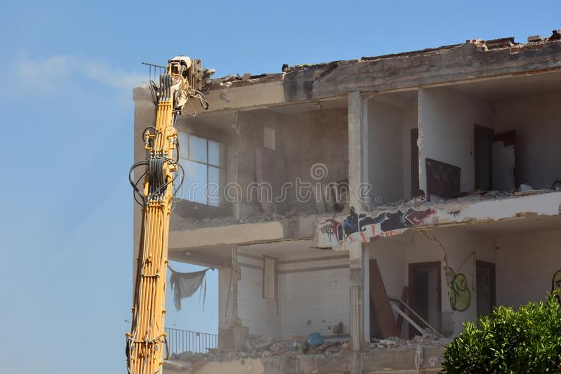 Arm of machine demolishing an apartment building. Large machine demolishing walls and pillars of an old residential building royalty free stock images
