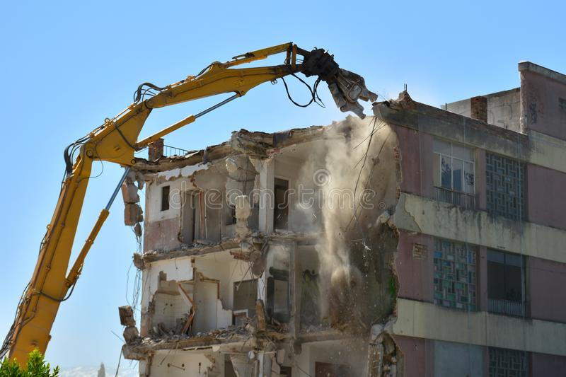 Arm of machine demolishing an apartment building. Large machine demolishing walls and pillars of an old residential building stock photo