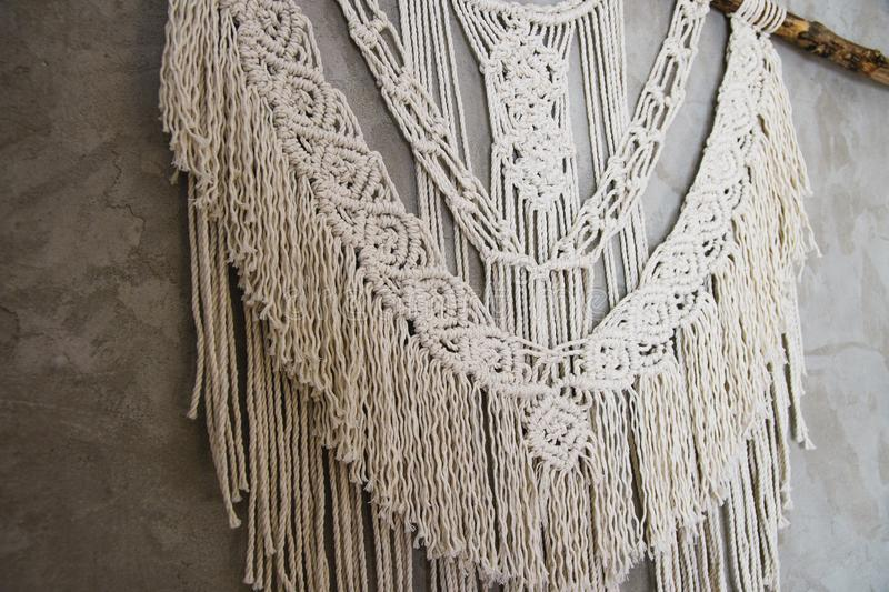 Large Macrame Wall Hanging. Wall panel in the style of Boho made of cotton threads in natural color using the macrame technique for home decor and wedding stock photo