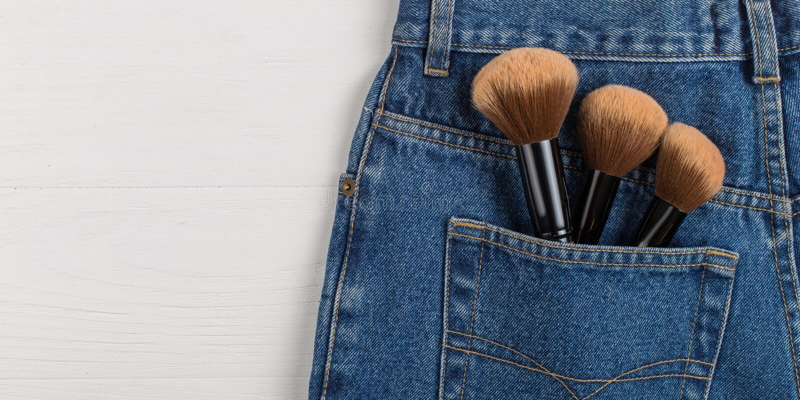 Large makeup brushes in a pocket of blue jeans. Concept, commercial work of a makeup artist, for printing business cards and stock images