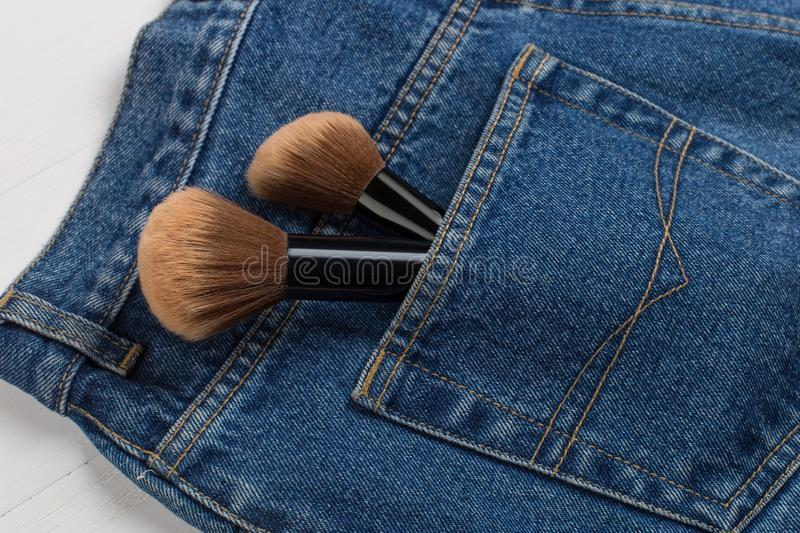 Large makeup brushes in a pocket of blue jeans. Concept, commercial work of a makeup artist, for printing business cards and. Large makeup brushes in pocket of royalty free stock photo