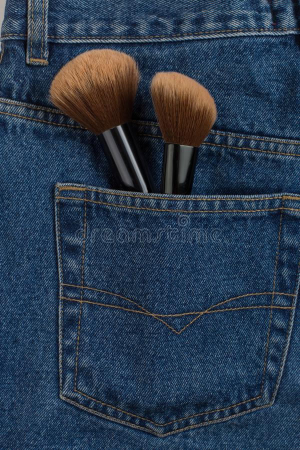 Large makeup brushes in a pocket of blue jeans. Concept, commercial work of a makeup artist, for printing business cards and royalty free stock image