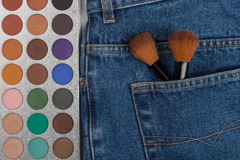 Large makeup brushes in a pocket of blue jeans. Concept, commercial work of a makeup artist, for printing business cards and royalty free stock photography