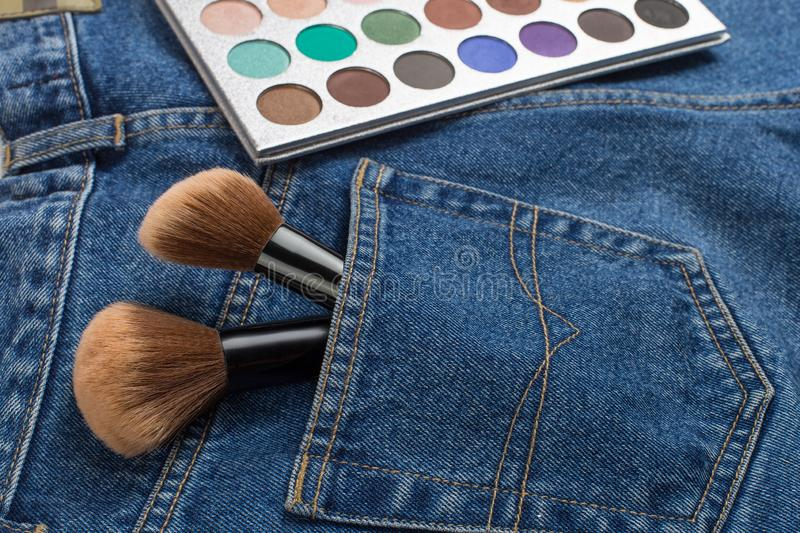 Large makeup brushes in a pocket of blue jeans. Concept, commercial work of a makeup artist, for printing business cards and. Large makeup brushes in pocket of stock photography