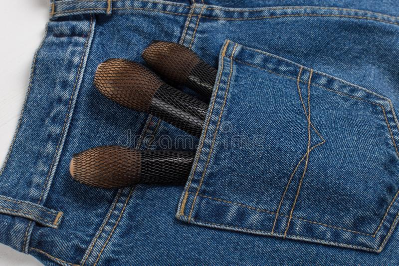 Large makeup brushes in a pocket of blue jeans. Concept, commercial work of a makeup artist, for printing business cards and. Large makeup brushes in pocket of stock images