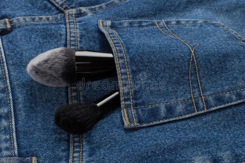 Large makeup brushes in a pocket of blue jeans. Concept, commercial work of a makeup artist, for printing business cards and. Large makeup brushes in pocket of stock image