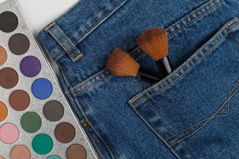 Large makeup brushes in a pocket of blue jeans. Concept, commercial work of a makeup artist, for printing business cards and. Large makeup brushes in pocket of royalty free stock photos