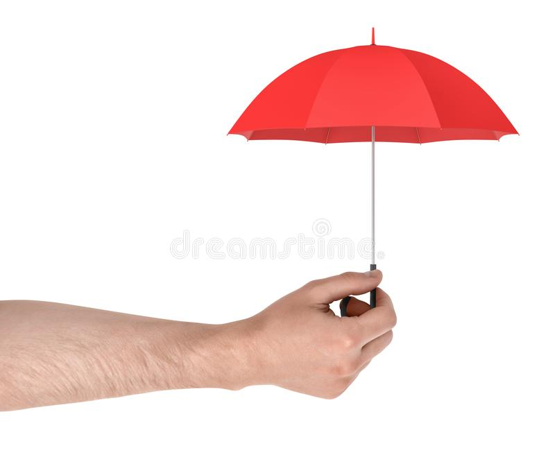 A large male arm holds a tiny red open umbrella isolated on a white background. royalty free stock photography