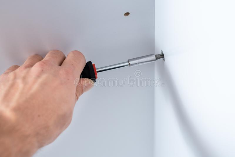 Large male hand with a manual screwdriver point in the Assembly of furniture. Close-up of a man`s hand with a manual screwdriver twists the bolt into a piece of royalty free stock photo