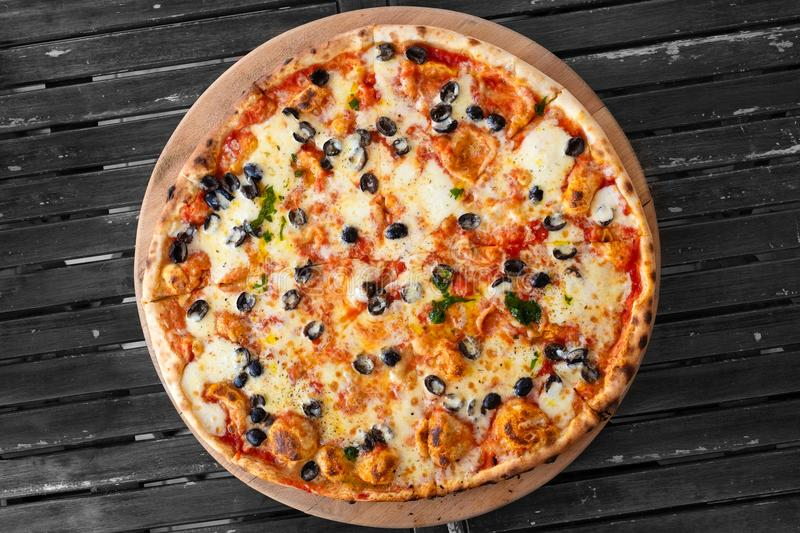 Large margherita pizza with black olives isolated on grey wood t royalty free stock photo