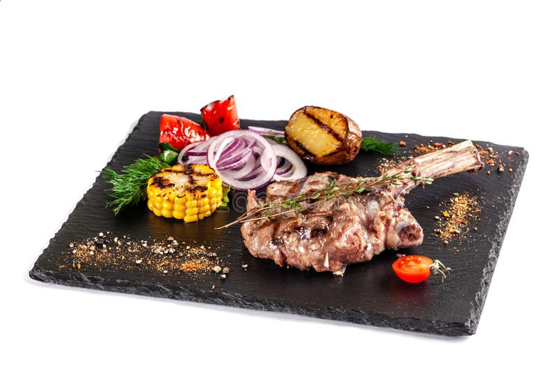 Large meat steak on the bone, grilled, served with grilled vegetables, corn, red onion, sweet peppers, potatoes. Modern serving. Dishes in the restaurant on a royalty free stock photography