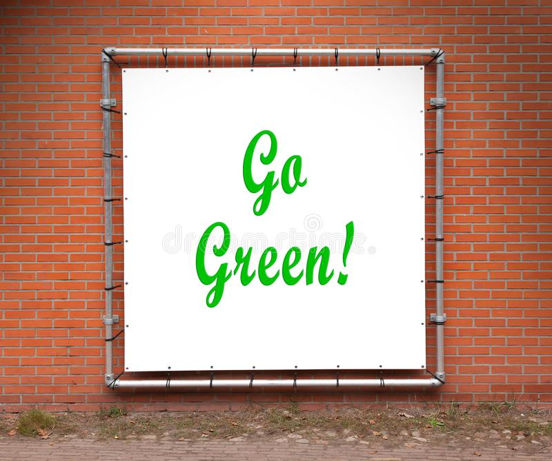 Large message written on a wall - Go green. Large message written on white plastic, on a wall - Go green royalty free stock images