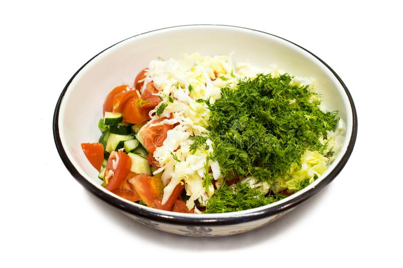 Large metal bowl of vegetable salad from tomato, cucumber, cabbage and greens isolated on white background. Healthy royalty free stock images