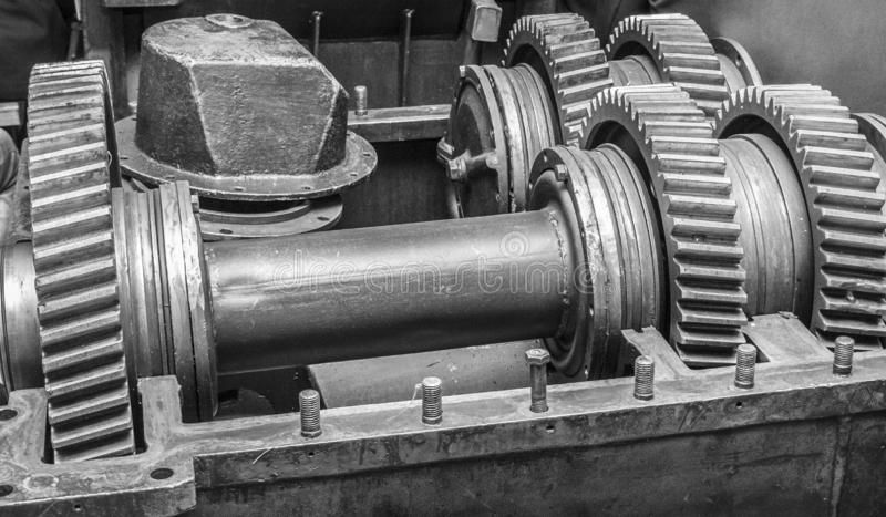 Large metal gears on large shafts in the mechanism housing. Large metal gears on large shafts in the body of the mechanism black and white royalty free stock image