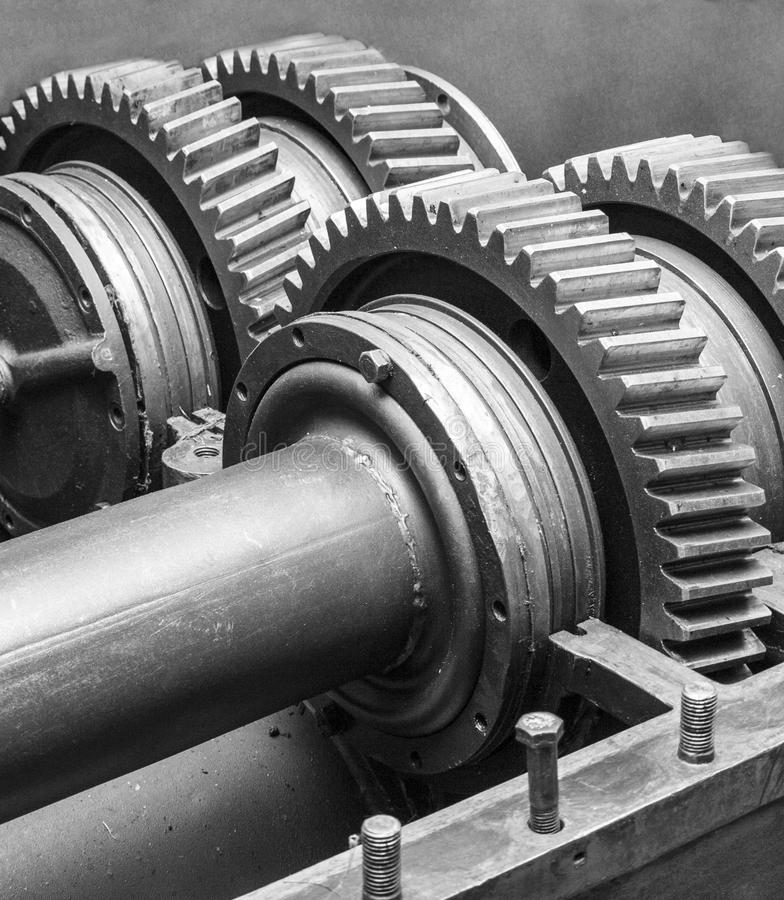 Large metal gears on large shafts in the mechanism housing. Large metal gears on large shafts in the body of the mechanism black and white stock images