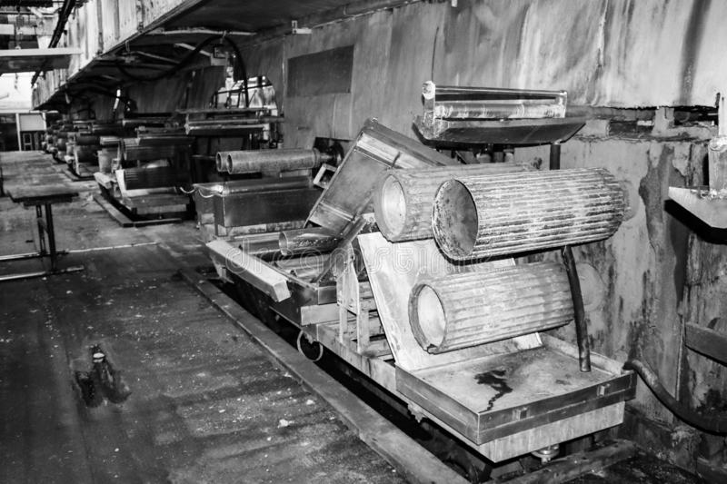 Large metal rollers rolls with teeth of the gears of the production line, a conveyor belt in the workshop at a industrial chemical royalty free stock photos