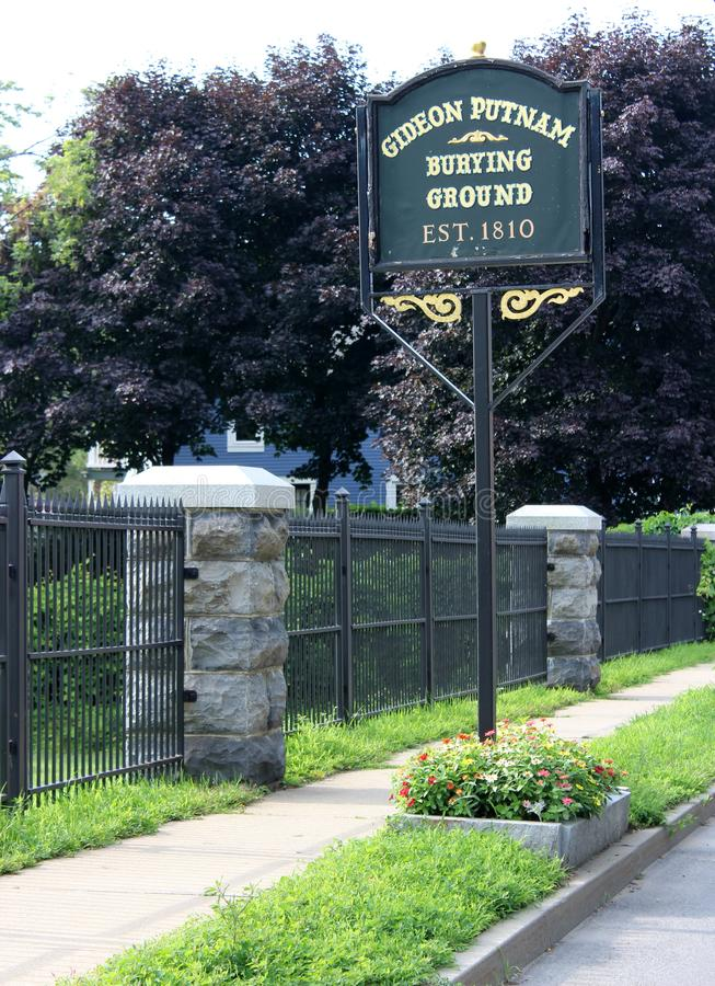 Large metal sign outside fenced in area of historic Gideon Putnam Burying Ground, Saratoga Springs, New York, 2018. Black wrought iron fencing surrounding royalty free stock photo