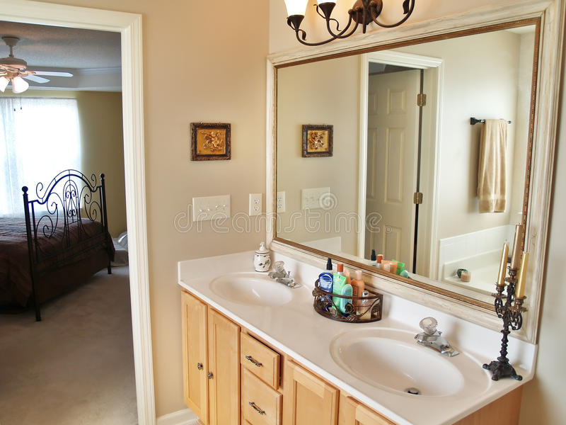 Large Mirror. A modern luxurious bathroom with a large in an American home. A bed is visible through the doorway in the background royalty free stock image