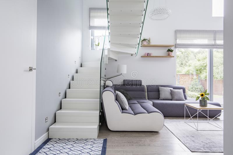 Large, modern sofa in a white living room interior with natural. Light and stylish staircase with glass barricade Concept royalty free stock photo