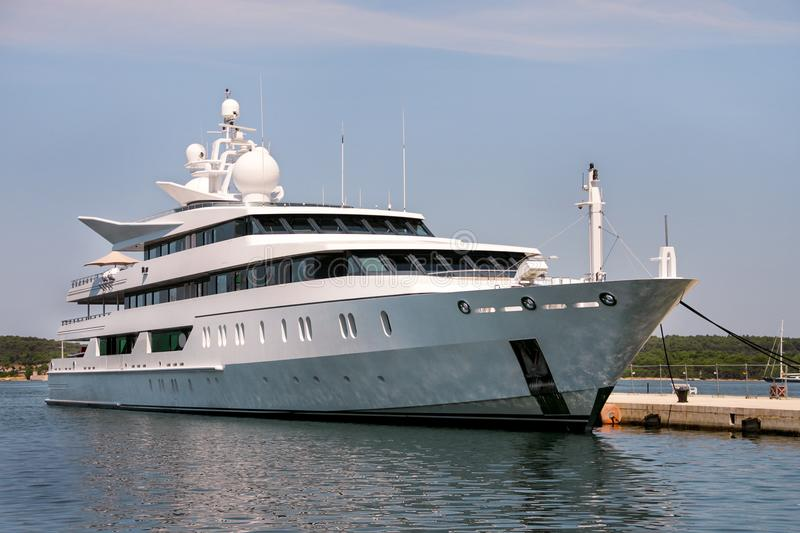 Large modern white yacht anchored in harbor stock images