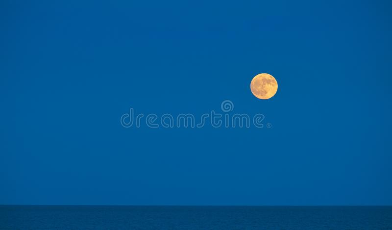 Large moon in a blue skyover the sea in the Natural park in Corralejo Fuerteventura Las Palmas Spain. Large glowing moon in a blue skyover the sea in the Natural stock photos