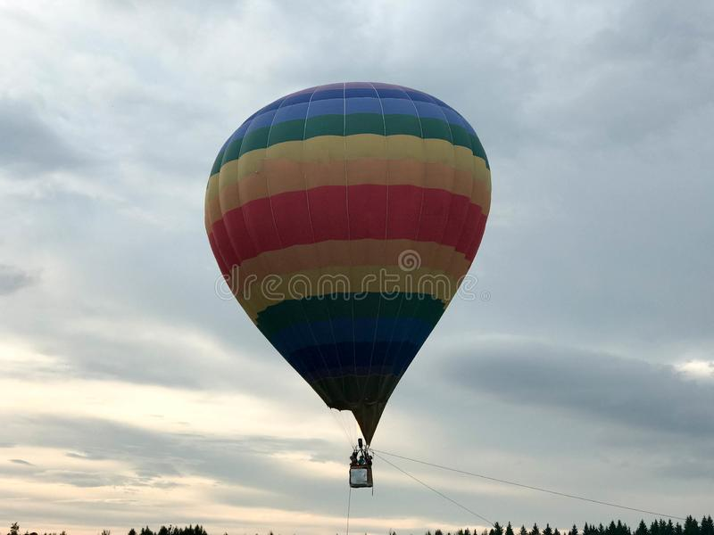 Large multi-colored bright round rainbow colored striped striped flying balloon with a basket against the sky in the evening stock image