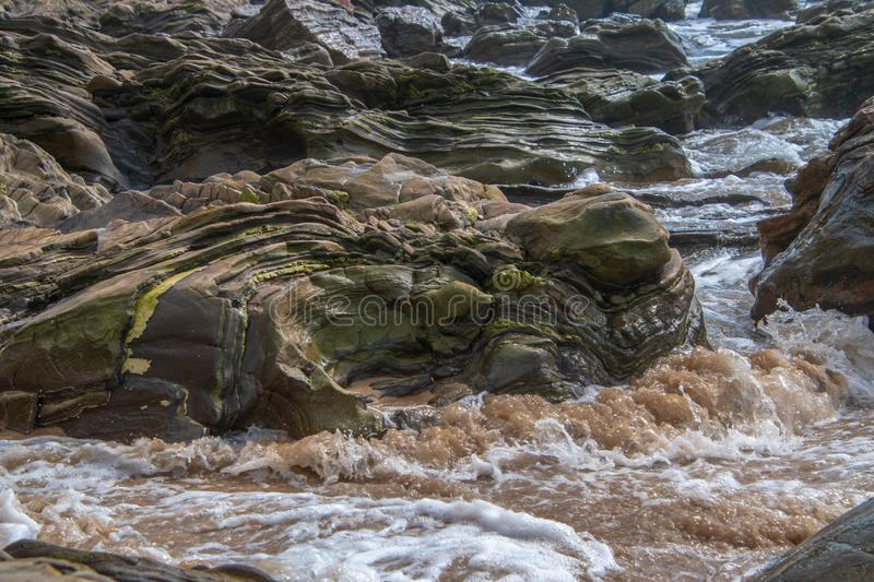 Large multi-layered boulder on beach with ocean waves hitting it as they approach the shore. stock photography