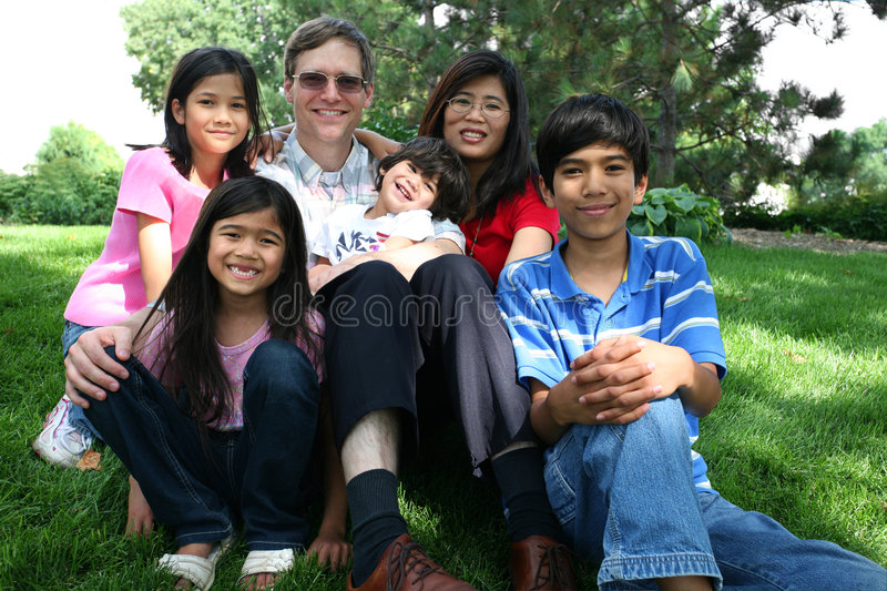 Large multiracial family sitting on lawn stock image