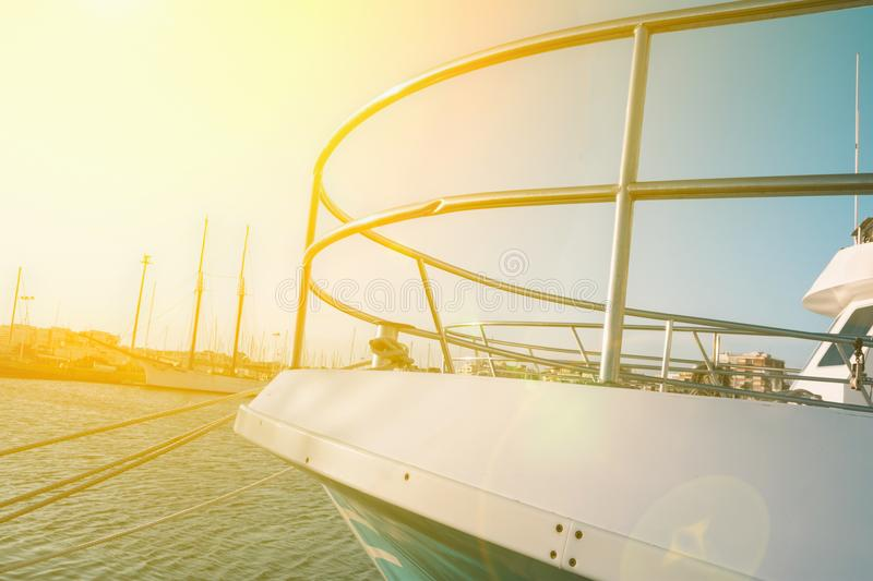Large New Beautiful Yacht Moored in Dock at Mediterranean Sea. Latral Side View of Boat Bow Nose. Bright Golden Sunlight Flare stock photos