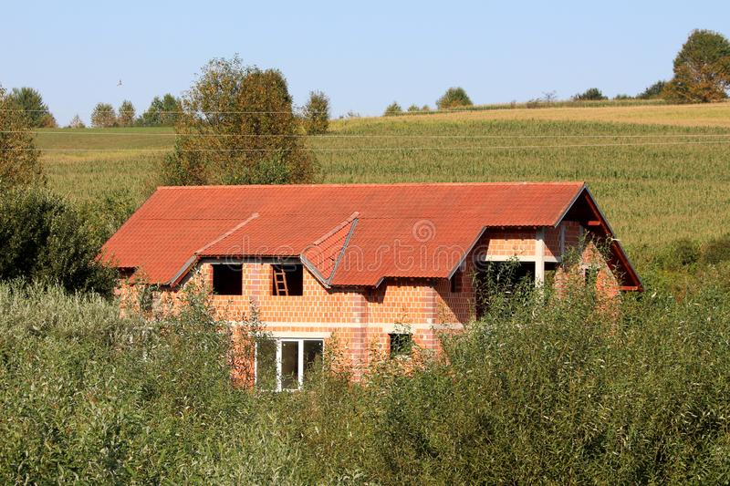 Large new unfinished red brick family house still under construction with new roof tiles and without windows completely surrounded royalty free stock photo