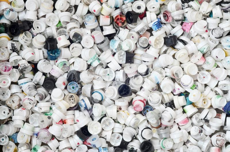 A large number of caps from cans of aerosol paint for graffiti. Smeared with colored paint nozzles lie in a huge pile stock images