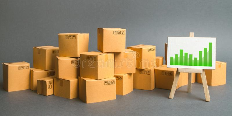 A large number of cardboard boxes and sign with green positive trend chart. rate growth of production of goods and products. Increasing economic indicators royalty free stock photo