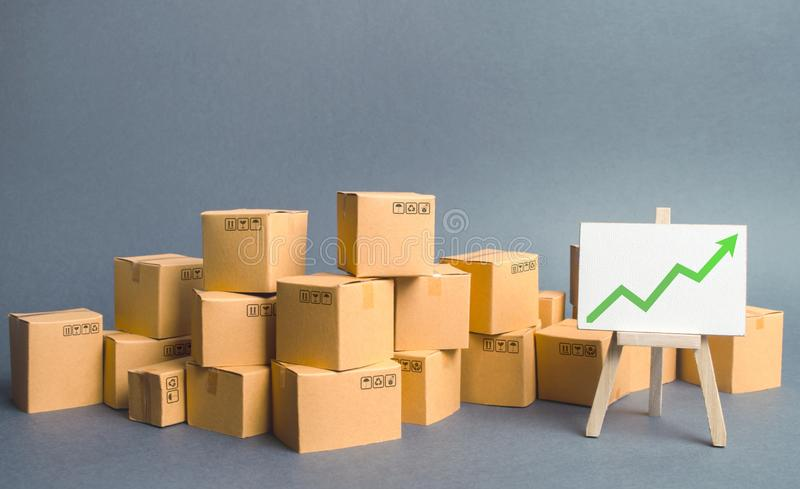 A large number of cardboard boxes and sign with green up arrow. rate growth of production of goods and products, increasing. Economic indicators. Increasing royalty free stock photography