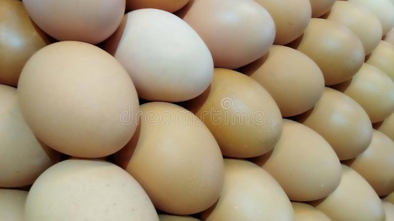 A large number of eggs that are stacked and have a rounded shape and brown color with a close-up view. Background royalty free stock photo