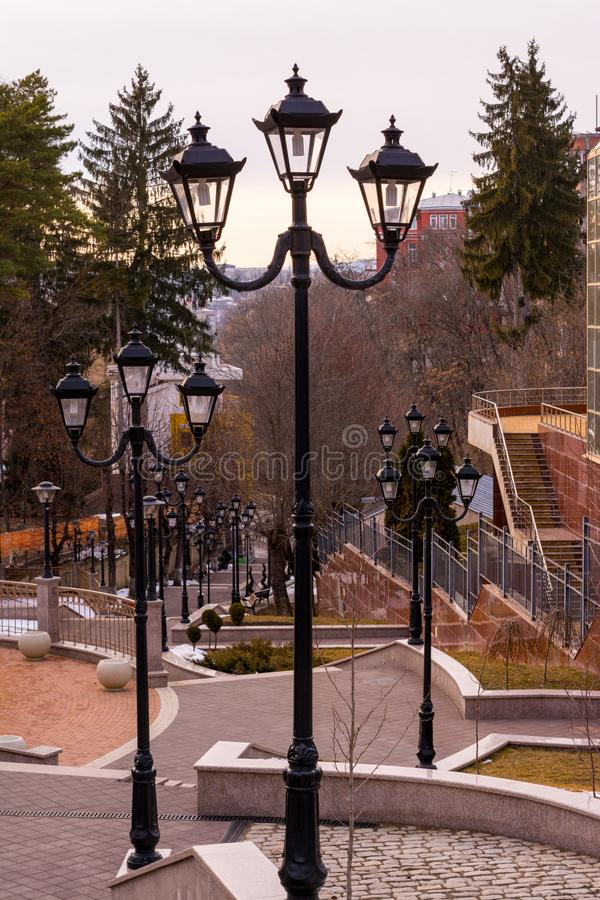 A large number of night lanterns on the sides of a tiled staircase leading down - a resort town, cityscape. Lamps, street, stairs, antique, vintage royalty free stock photos