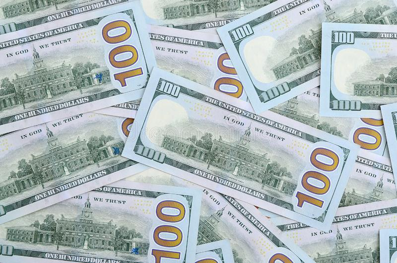 A large number of US dollar bills of a new design with a blue stripe in the middle. Top view.  royalty free stock photo
