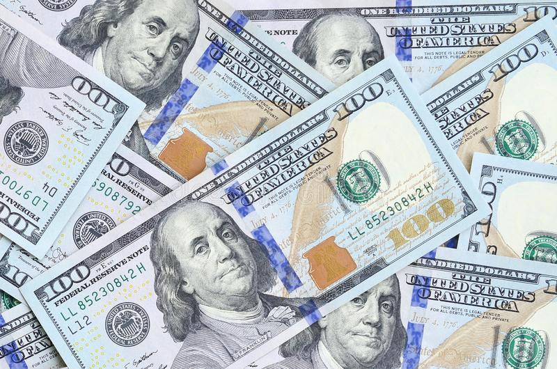 A large number of US dollar bills of a new design with a blue stripe in the middle. Top view.  stock photo